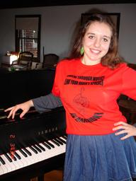 Young soprano singer CHARLOTTE KHUNER (16 y.o.), after rehearsal for the upcoming NAMM Show performance in LA, CA, USA; by her piano in t-shirt with the advocacy for music education through brain research message for the for the int'l campaign  http://www.youtube.com/watch?v=rLtLBIxMYgo